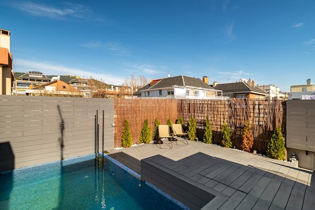 Private terrace on the roof of a house with swimming pool sunbeds and wooden fence on sunny day in b...