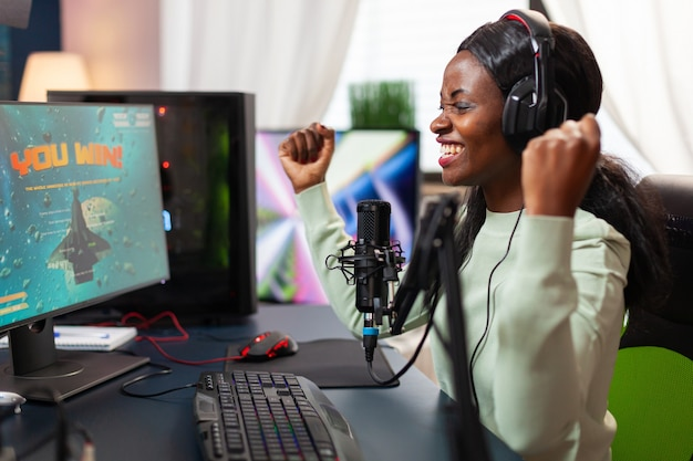 Pro african esport streamer excited after wining video games championship screaming into microphone. online streaming cyber performing during video games tournament in home with neon lights.