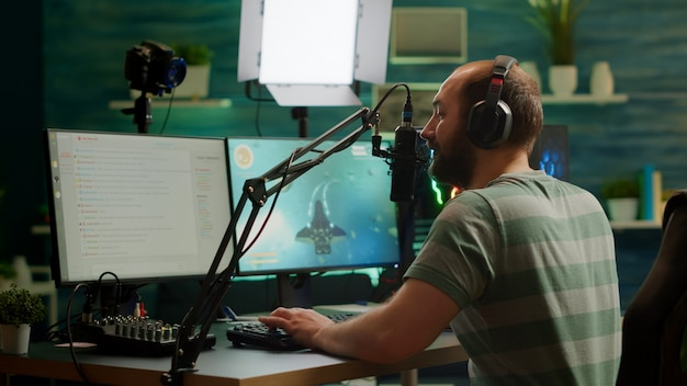 プロのサイバーマンストリーミングビデオゲーム、ストリームチャットでの読書、rgbパワフルなコンピューターでのスペースシューターのプレイ。オンラインeスポーツトーナメント中にゲームをプレイするゲーミングチェアに座っているストリーマー。