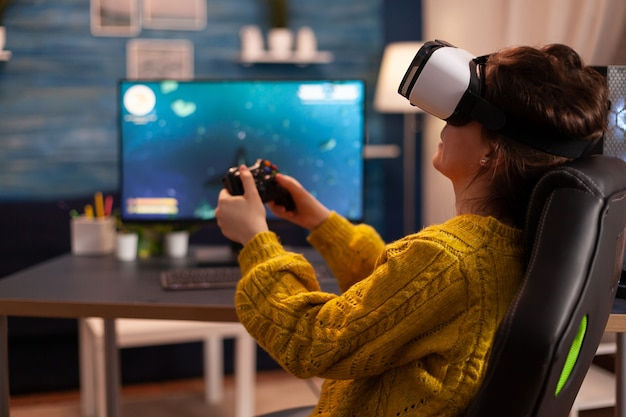 Профессиональный киберспортсмен, расслабляющий, играя в видеоигры, используя гарнитуру vr, поздно ночью