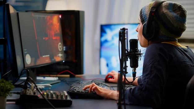 Pro cyber donna che parla al microfono professionale in streaming nello studio domestico di gioco con chat in streaming aperto. giocatore che si esibisce in un torneo online utilizzando un potente personal computer con rgb e auricolare