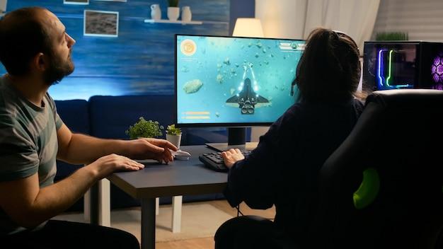 Пара профессиональных геймеров играет в космические шутеры, сидя на игровом чаре в наушниках