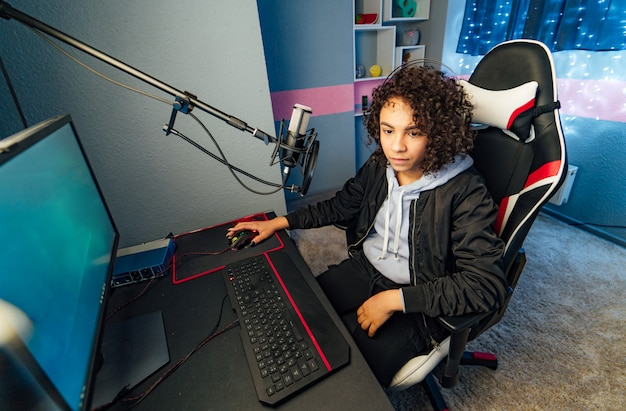 Снимок прекрасной pro gamer girl, играющей в онлайн шутер от первого лица на своем персональном компьютере. неоновая комната. кибернетические игры интернет