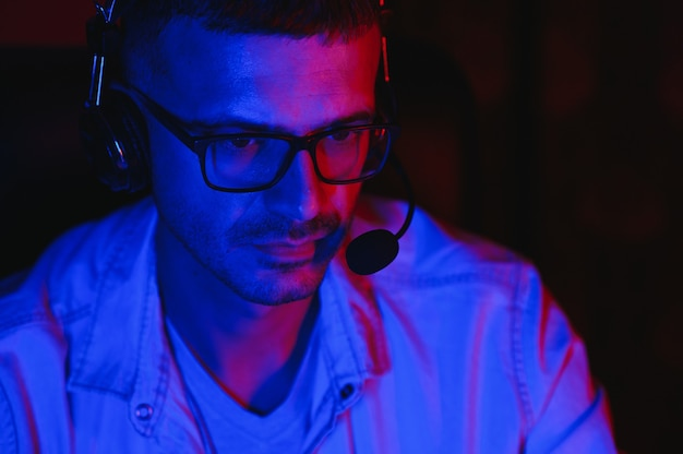 Профессиональный игрок. парень из поколения миллениума, сидящий ночью дома, на настольном компьютере, играя в онлайн-видеоигру. неоновые огни, выборочный фокус