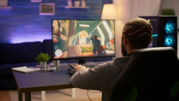Rgb 마우스 키보드를 사용하여 게임 홈 스튜디오에서 1인칭 슈팅 비디오 게임을 하는 프로 게이머. 게임 토너먼트 중 네온 불빛 사이버가 실행되는 가상 온라인 스트리밍 설정