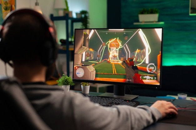 Профессиональный геймер, играющий в виртуальный шутер для онлайн-соревнований в профессиональных наушниках. онлайн-трансляция кибер-выступления во время игрового турнира с использованием технологии беспроводной сети