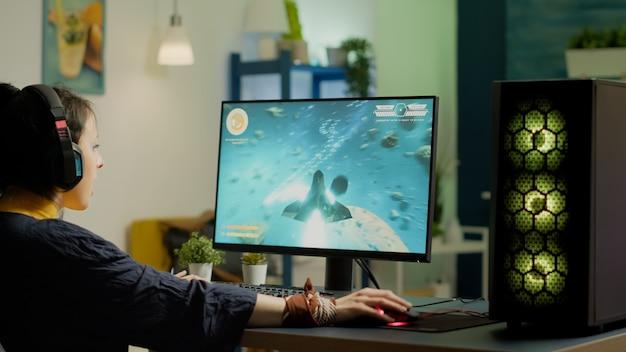 심야 라이브 토너먼트를 위해 rgb 강력한 컴퓨터 재생 공간 사수 비디오 게임을 사용하여 게임실에서 새로운 그래픽으로 온라인 비디오 게임을 스트리밍하는 프로 게이머. e스포츠 프로선수