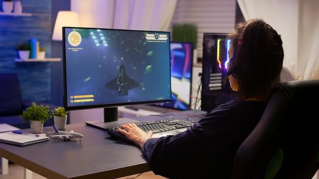Профессиональный геймер разговаривает в микрофон с другими игроками во время цифрового чемпионата