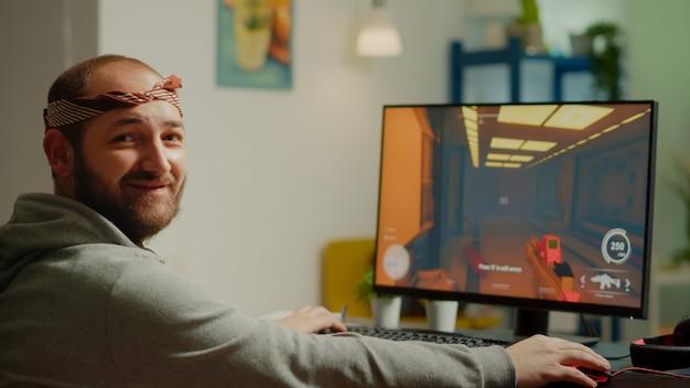프로 남자 게이머는 사이버 공간에서 게임 챔피언십 동안 fps 슈팅 비디오 게임을 하며 웃고 있는 카메라를 바라보며 고개를 돌립니다. 온라인 토너먼트에서 강력한 컴퓨터에서 수행하는 e스포츠 선수