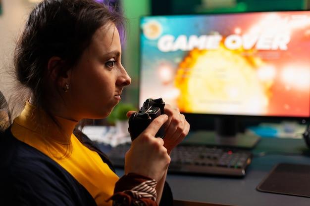 机のゲーミングチェアに座って、コンソールを使用してスペースシューティングビデオゲームを失うプロプレーヤー。ネオンライトのある部屋でeスポーツトーナメントのオンラインビデオゲームをストリーミングする女性