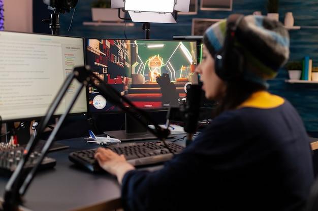 프로 스트리머는 헤드폰을 사용하고 게임 채팅이 열린 상태에서 강력한 모니터를 들여다봅니다. 기술 네트워크 무선을 사용하여 가상 토너먼트를 수행하는 온라인 스트리밍 사이버