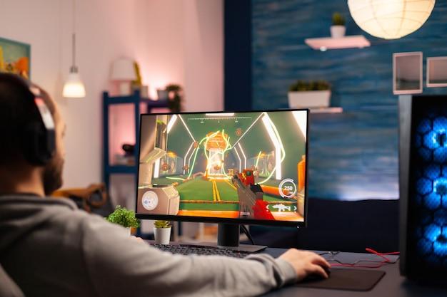 Профессиональный виртуальный геймер в наушниках играет в видеоигры на профессиональном компьютере поздно ночью. онлайн-трансляция кибер-выступления во время игрового турнира с использованием технологии беспроводной сети