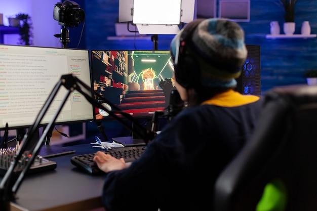 게임 홈 스튜디오에서 헤드폰 스트리밍 비디오 게임을 하는 프로 여성 게이머. 강력한 컴퓨터에서 게임 경쟁을 위해 온라인으로 다른 플레이어와 이야기하는 전문 플레이어