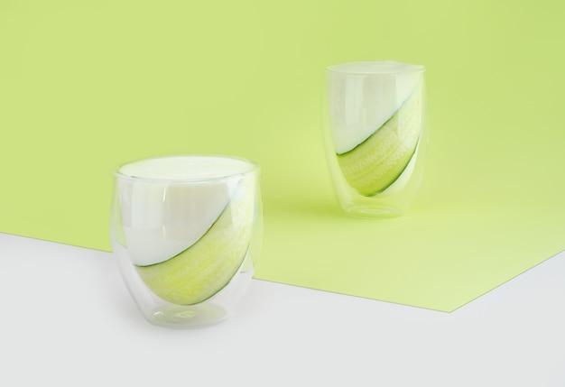 프로바이오틱 음료, 버터밀크 또는 요구르트. 최소한의 아이소메트릭 대각선 녹색 배경에 유리에 케피어와 오이. 박테리아 장 건강, 위장관을 위한 발효 제품. 공간을 복사합니다.