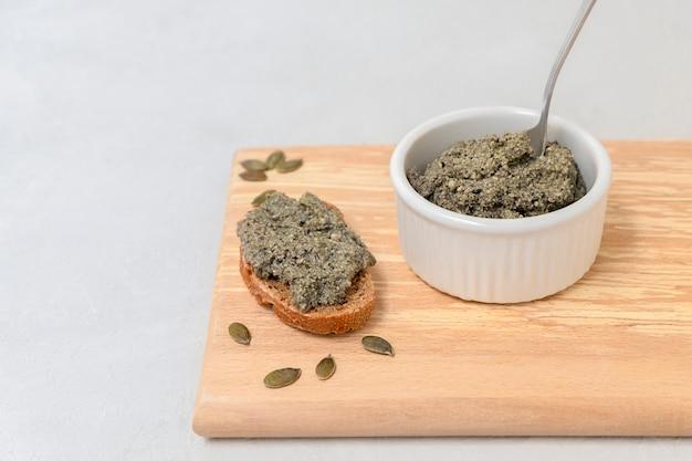 カボチャの種から作られたプロバイオティックカルチャーのビーガンチーズペーストをコピーでパンのスライスの上に広げます...