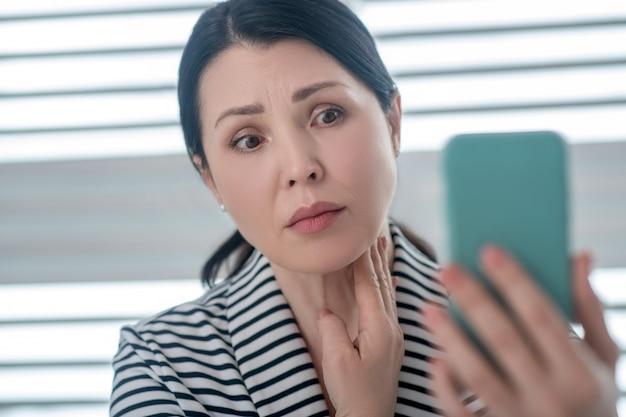 問題。彼女の手でスマートフォンの画面を注意深く見ている気になる大人のブルネットの女性。