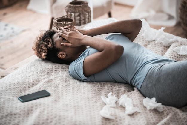 問題、泣いています。寝室で泣いているスマートフォンでベッドに横たわっている手で彼女の顔を覆っている浅黒い肌の若い大人の女性