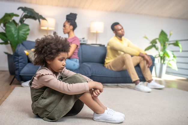 Problem, family. profile of dark-skinned little sad daughter sitting on floor and unhappy parents turned away from each other on couch