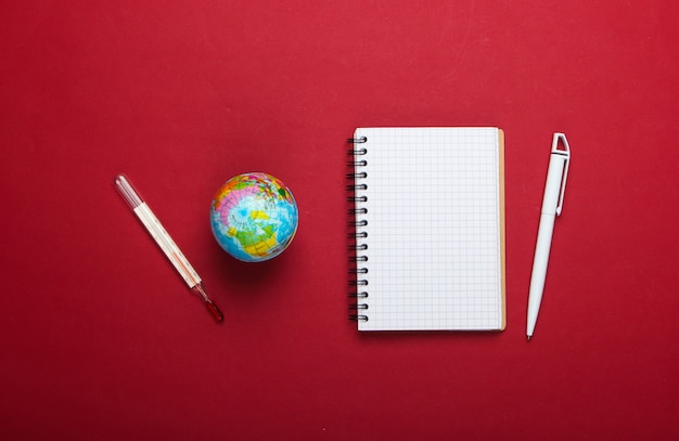 The problem of global warming. globe, thermometer with notebook on red background. top view