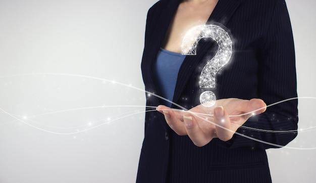 問題、助けの必要性とアドバイスの概念。手持ちデジタルホログラム疑問符、灰色の背景に記号。オンラインで答えを見つける、faqの概念、何を、いつ、どのように、そしてなぜ、情報を検索する