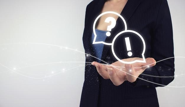 問題、助けの必要性とアドバイスの概念。灰色の背景にオンラインでデジタルホログラムquiestionsを手に持ってください。質問と混乱の概念。
