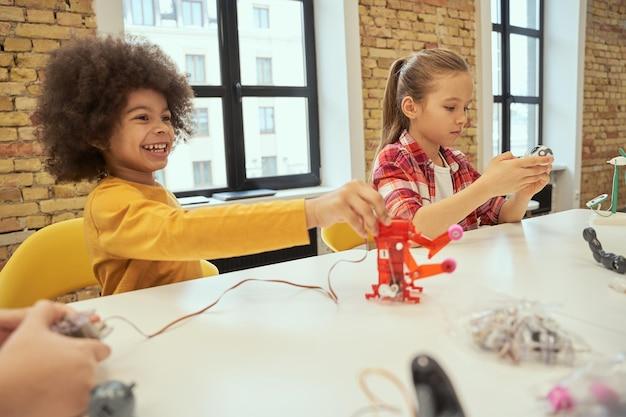 Решение задач. любопытные маленькие дети, которые с интересом смотрят на технические игрушки, сидя за столом