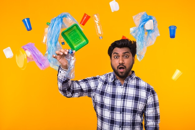 Problem of trash, plastic recycling, pollution and environmental concept - surprised indian man holding crumpled plastic bottle on yellow wall.