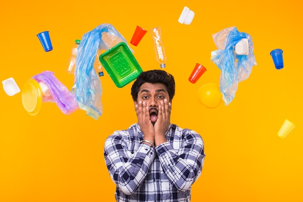 Problem of trash, plastic recycling, pollution and environmental concept - terrified indian man surronded by trash