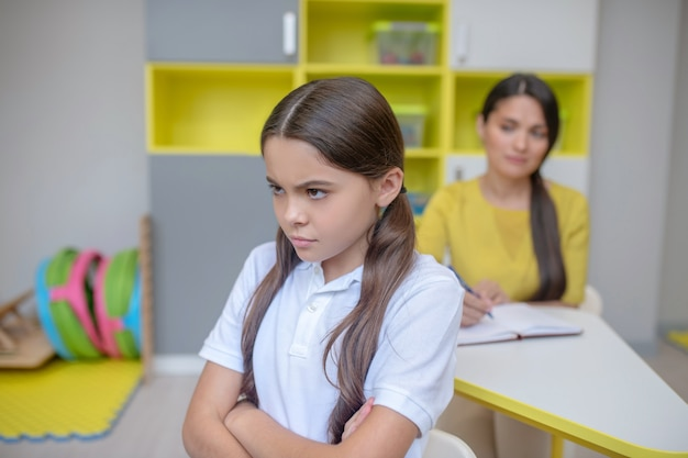 問題。胸に腕を組んで立っている白いtシャツと後ろに座っている女性心理学者の動揺した長い髪の少女