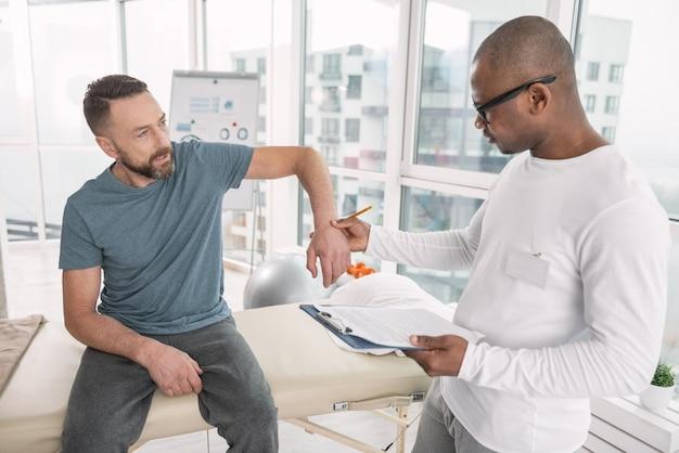 筋肉の問題。彼の腕を見せながら彼の医者を見て楽しいひげを生やした男