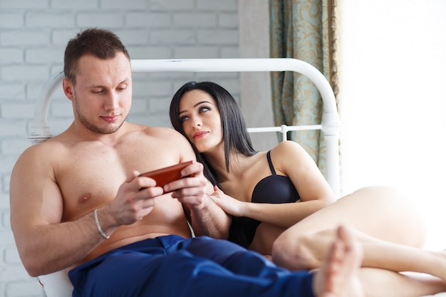 Problems in the family. angry young woman lying on the bed, against her husband, who plays the game on the phone.
