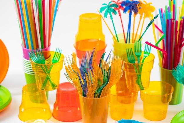 環境の問題。プラスチック製の明るいフォークを透明なカップに入れ、危険なストローがエコロジーの大惨事になっている