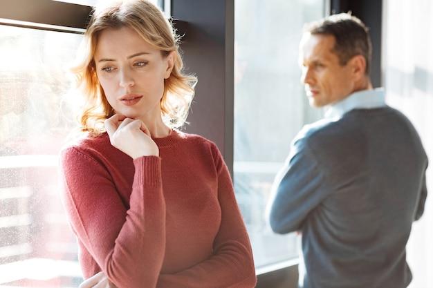 人間関係の問題。彼氏の近くに立って落ち込んでいる間彼女のあごを保持している悲しい不幸な元気のない女性