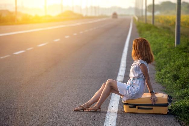 Проблемы в путешествии. девушка сидит на желтом чемодане на обочине дороги