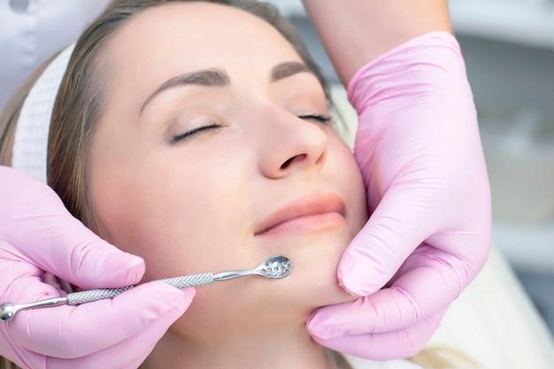 블랙 헤드와 여드름의 숟가락으로 강철 제품으로 얼굴 피부를 청소하는 절차.