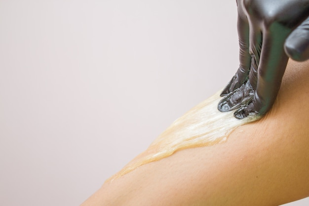 Procedure of hair removing on leg beautiful woman with sugar paste or wax honey and black gloves hand