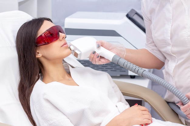 Procedure of photoepilation in the beauty salon. young woman receiving epilation laser treatment on face at beauty center close up
