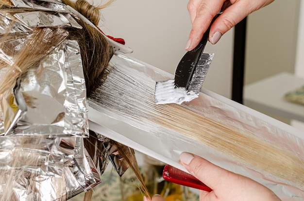 Process of applying bleaching powder on clients hair and wrapping into the foil. airtouch technique