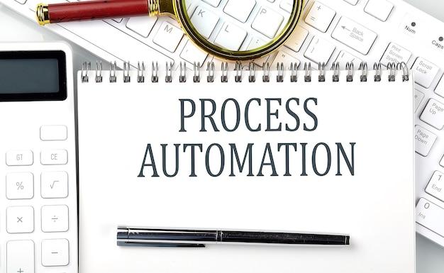 プロセスの自動化。電卓とキーボード、ビジネスコンセプトとメモ帳のテキスト