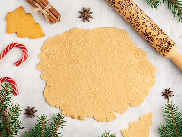 Process of baking traditional christmas and new year dessert , gingerbread cookies ,rolling pin with snowflakes pattern on it, anise stars and cinnamon
