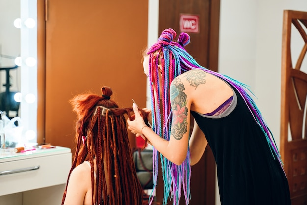 Process of braiding the master weaves braids on her head in a beauty salon