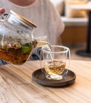 Процесс заваривания чая. горячий травяной или зеленый чай с мятой и лепестками роз.