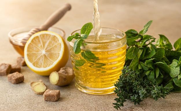 醸造茶を処理します。ミント、タイム、ジンジャー、レモン、ハチミツを添えた温かいハーブティーまたはグリーンティー。