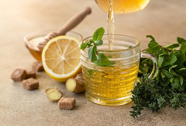 醸造茶を処理します。ミント、タイム、生姜、レモン、蜂蜜入りの温かいハーブティーまたは緑茶。