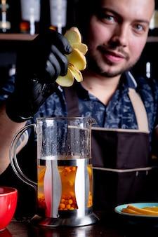 お茶、茶道を醸造するプロセス。バーテンダーがスライスしたジンジャーをケトルに加えて海のフルーツティーを醸造