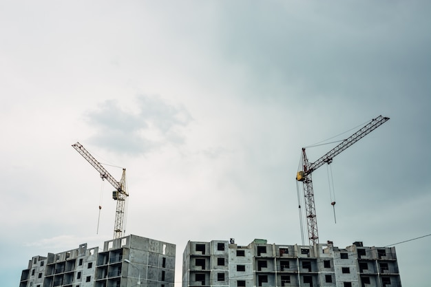 The process of building a multi-storey building. lifting cranes against the sky.