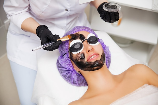 Process of carbon face laser peeling procedure in beauty salon. laser pulses clean skin of the face. hardware cosmetology treatment. skin rejuvenation. young woman with carbon nanogel on her face