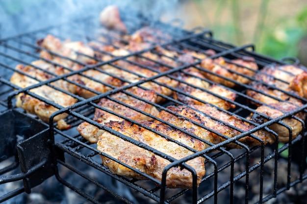 肉のステーキを屋外のバーベキューグリルで調理するプロセス。ピクニック、屋外での食事。金属製バーベキューグリル