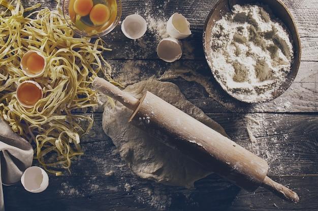 Processo di cottura di pasta con ingredienti freschi crudi per il classico cibo italiano - uova crude, farina su tavola di legno. vista dall'alto. tonificante.
