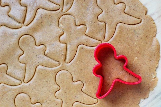 Process of dealing with gingerbread man cookies, use red gingerbread man mold cutting gingerbread dough on baking paper around colorful cookie cutters on white wooden table. top view